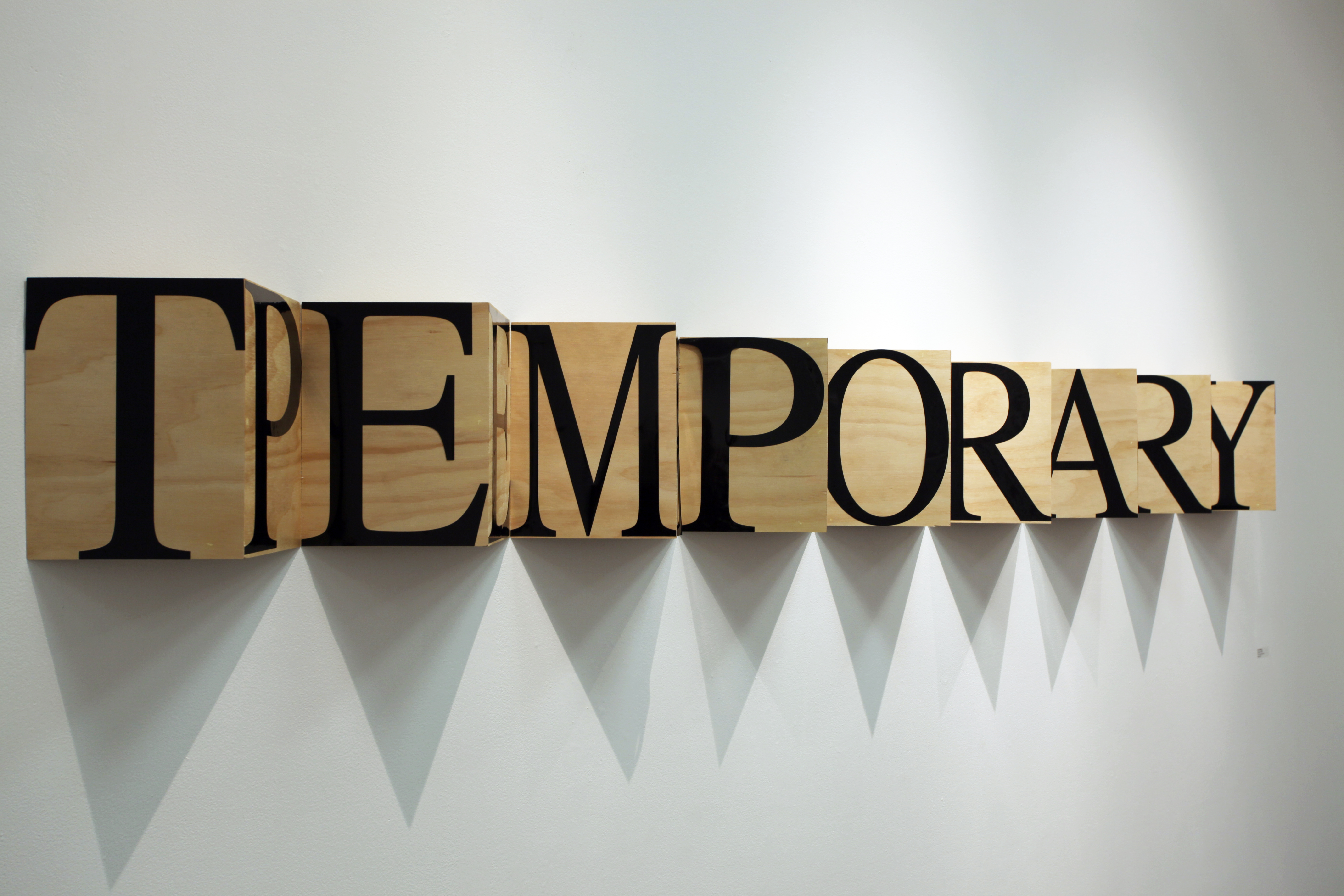 "Wall sculpture of the words ""temporary"" and ""permanent"" mashed up so as to each only be viewable from the side"