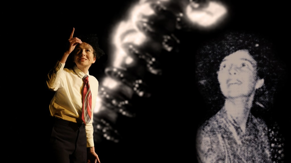 Female performer, wearing a 1930s man's dress shirt and tie and a woman's hat, looks intently and joyfully at her raised finger before a projected image of electricity arcing and a 1930s photos of a young woman in a similar pose.